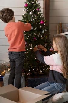 Rodzeństwo wspólnie dekoruje choinkę