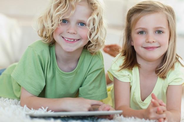Rodzeństwo za pomocą tabletu na podłodze