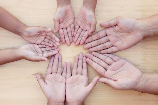 Rodzic i dzieci otwierają dłoń w kręgu, pokazując jedność i pracę zespołową
