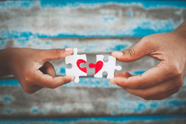 Rodzic i dziecko ręce łączenia kawałek układanki kawałek z ciągnione czerwone serce
