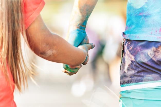 Rodzic i dziecko trzymają się za ręce i chodzą na holi paint party festival of colors holifest