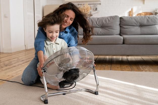 Rodzic i dziecko w domu wesoła młoda matka z małym synem cieszą się dmuchaniem chłodnego wiatraka w pomieszczeniu