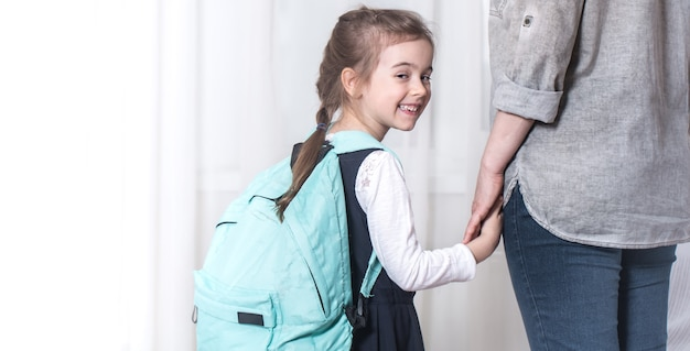 Rodzic i uczeń szkoły podstawowej idą w parze na jasnym tle. powrót do koncepcji szkoły