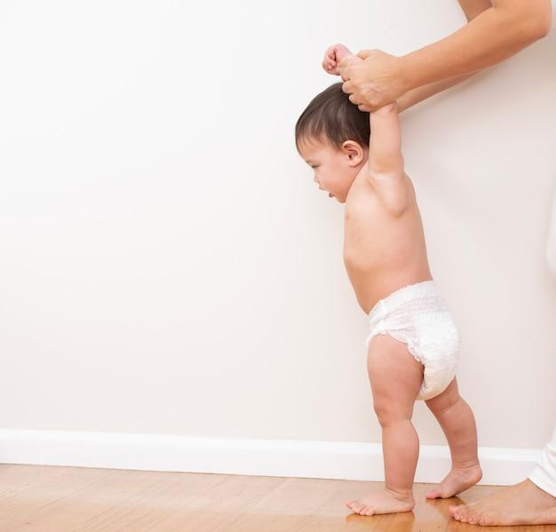 Rodzic pomaga dziecku chodzić, trzymając się za ręce i prowadząc wsparcie