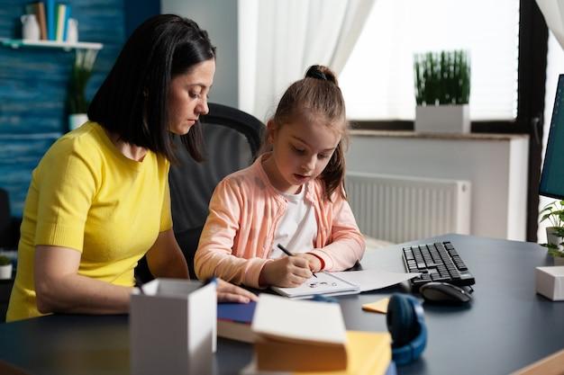 Rodzic pomaga małej córce w odrabianiu lekcji w szkole