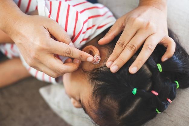 Rodzic pomaga swojemu dziecku dokonać urazu ucha pierwszej pomocy po wypadku