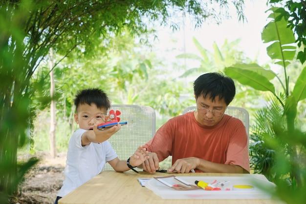 Rodzic siedzi w domu, ucząc się w domu z małym dzieckiem azjata, ojciec i syn bawią się, robiąc łódki z zabawkami dla majsterkowiczów