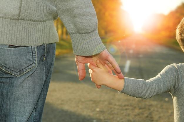 Rodzic trzyma za rękę dziecko idące w pobliżu drogi