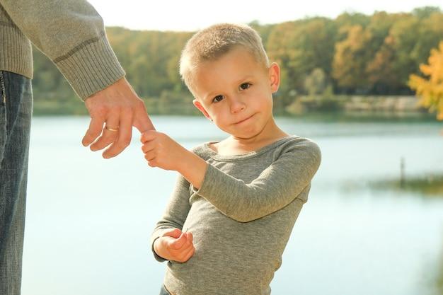 Rodzic trzyma za rękę szczęśliwego małego chłopca syna