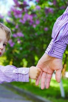 Rodzic trzymający dziecko za rękę ze szczęśliwym tłem