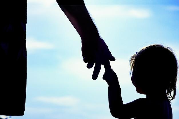 Rodzic z dzieckiem nad morzem sylwetka