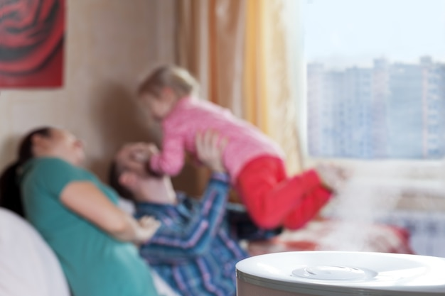 Rodzice bawią się z córką na rozmytym tle nawilżacza