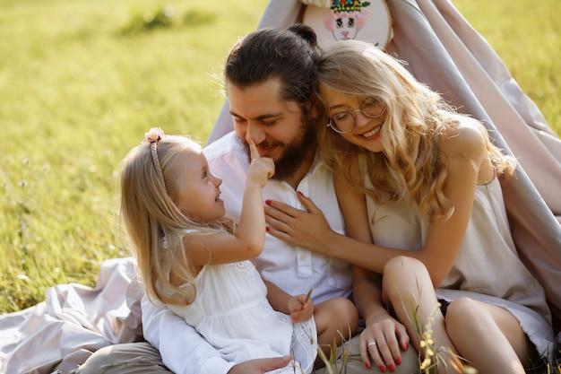 Rodzice bawią się z dzieckiem. córka jest blondynką. wieczorny spacer