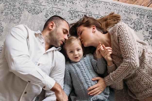 Rodzice całują córeczkę leżącą na podłodze w domu.