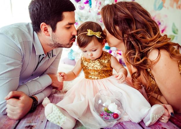 Rodzice całują małą dziewczynkę w złotej sukni
