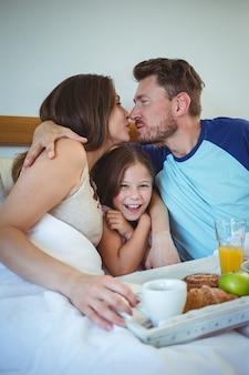 Rodzice całują siedząc na łóżku z córką i jedząc śniadanie