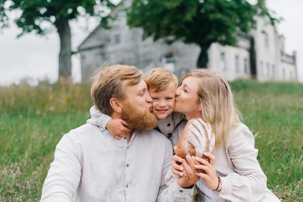 Rodzice całują syna w oba policzki. koncepcja szczęśliwej rodziny i naturalnych materiałów.
