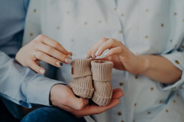 Rodzice czekają na dziecko. nie do poznania kobieta i mężczyzna trzymają buciki dla noworodka. spodziewaj się przed porodem. nowa koncepcja rodziny