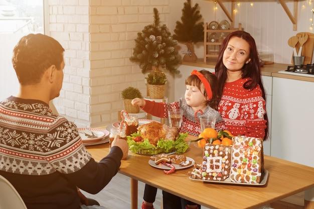 Rodzice i córeczka przy świątecznym stole słonecznym.