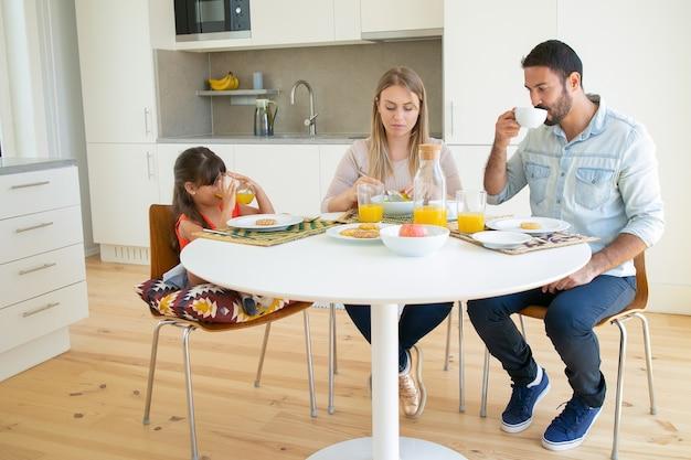 Rodzice i córka jedzą razem śniadanie, piją kawę i sok pomarańczowy, siedzą przy stole z owocami i ciastkami.