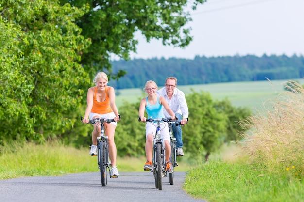 Rodzice i córka odbywają wycieczkę rowerową lub rowerową po wiejskiej drodze