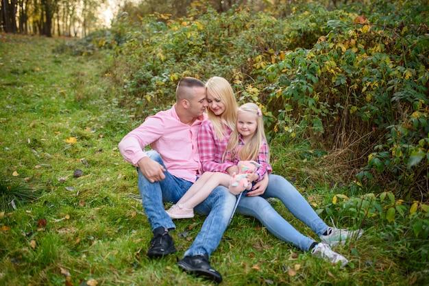 Rodzice i córka siedzą na trawie.