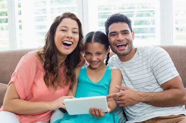 Rodzice i córka używa cyfrową pastylkę w żywym pokoju w domu