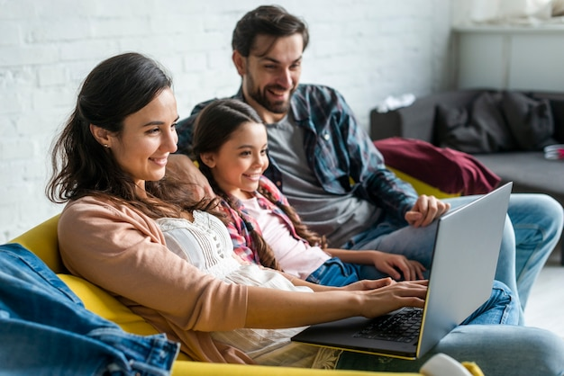 Rodzice i córka używa laptop