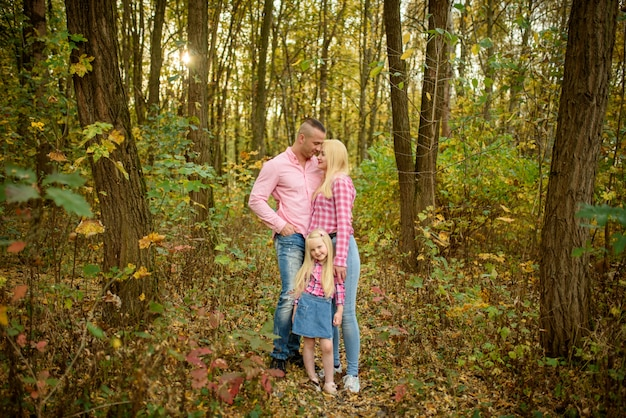 Rodzice i córka w jesiennym parku.