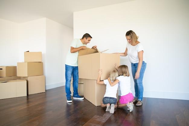 Rodzice i dwie córki bawią się podczas otwierania pudeł i rozpakowywania rzeczy w swoim nowym pustym mieszkaniu