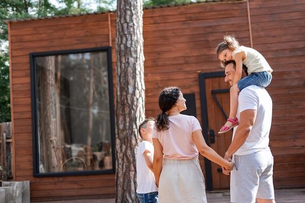Rodzice i dwoje dzieci stoją na podwórku córka siada na ramionach taty, z którymi się komunikują
