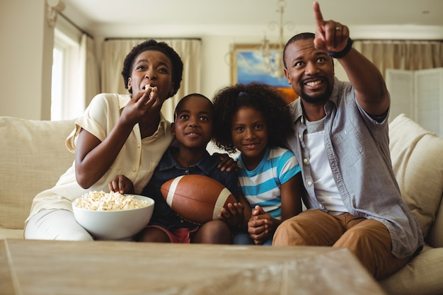 Rodzice i dzieci bawią się podczas oglądania telewizji w salonie