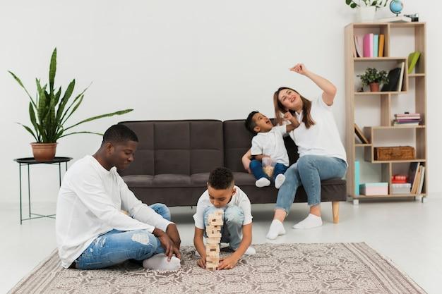 Rodzice i dzieci bawiące się razem w drewnianą wieżę