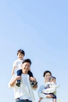 Rodzice i dzieci chodzą z uśmiechem pod błękitnym niebem