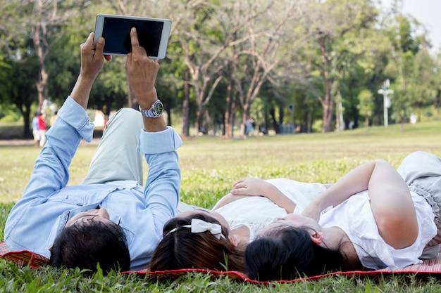Rodzice i dzieci grają na tablecie na macie w parku.