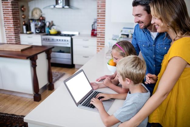 Rodzice i dzieci korzystające z laptopa w kuchni