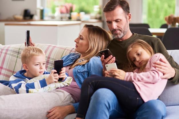 Rodzice i dzieci korzystające z telefonu komórkowego w salonie