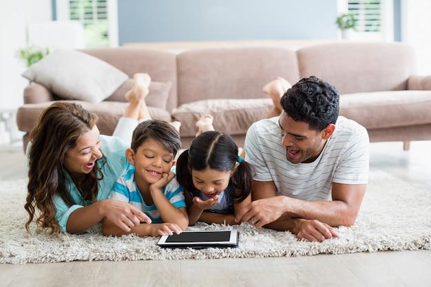 Rodzice i dzieci leżące na dywanie i korzystające z cyfrowego tabletu w salonie