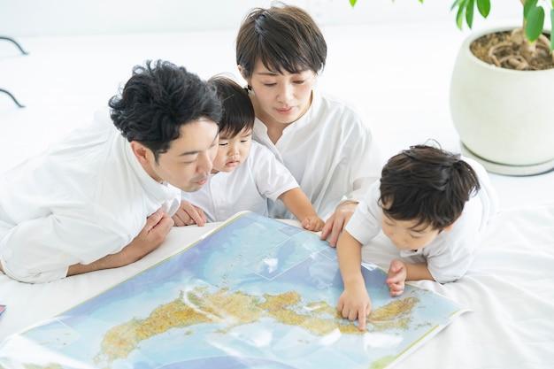 """Rodzice i dzieci radośnie uczące się przy użyciu map """"» rodzice i dzieci planujący wycieczki przy użyciu map"""