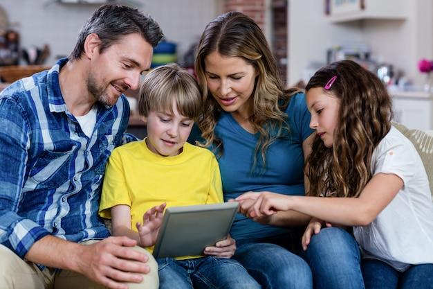 Rodzice i dzieci siedzą na kanapie i korzystają z cyfrowego tabletu