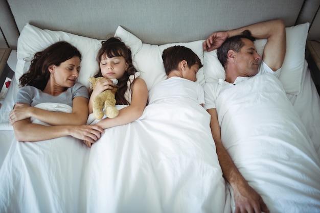 Rodzice i dzieci śpiące w łóżku