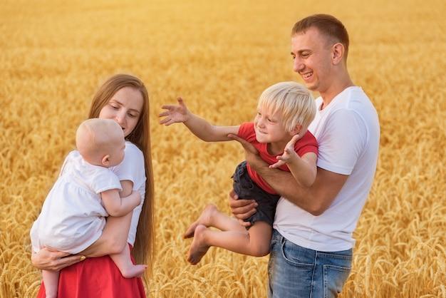 Rodzice i dzieci stojące na polu pszenicy