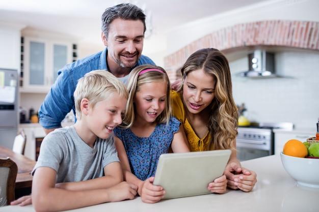 Rodzice i dzieci za pomocą cyfrowego tabletu w kuchni