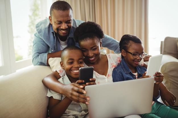 Rodzice i dzieci za pomocą laptopa, smartfona i cyfrowego tabletu na kanapie