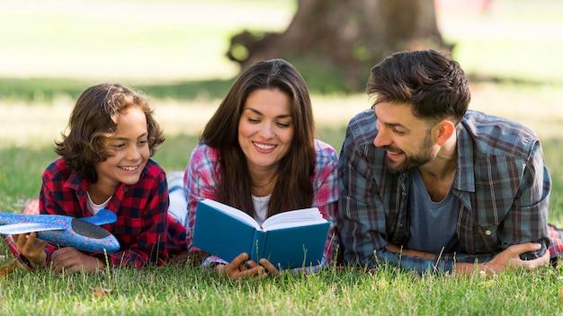 Rodzice i dziecko czytają razem na zewnątrz