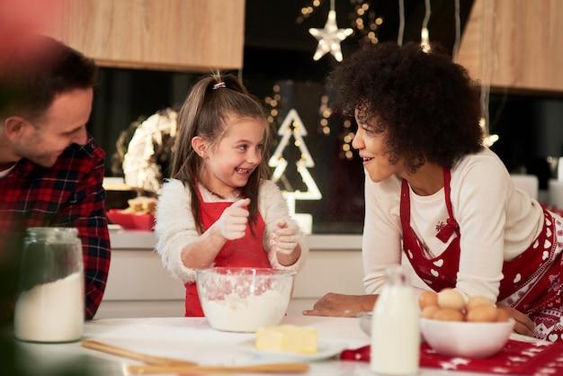 Rodzice i dziecko pieczą ciasteczka w kuchni