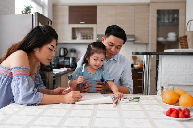 Rodzice i dziecko rysujące średnie ujęcie