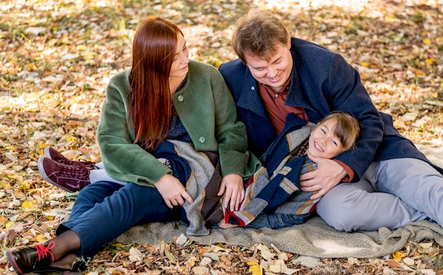 Rodzice i dziecko siedzi na kocu