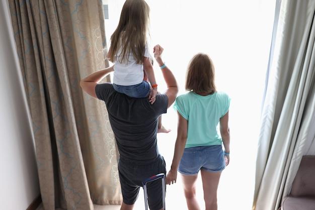 Rodzice i dziecko stoją w pokojach hotelowych i wyglądają przez okno