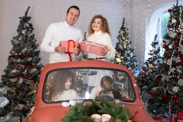Rodzice i ich dzieci bawią się w czerwonym samochodzie w pobliżu choinek.